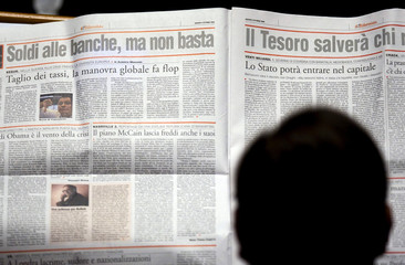 Deputy reads newspaper reading as Italy's Economy Minister Tremonti gives speech to lower house of Parliament in Rome