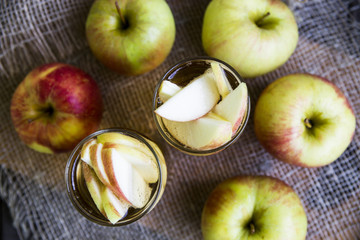 Apple cider with slices of apples in transparent glasses on a wooden board