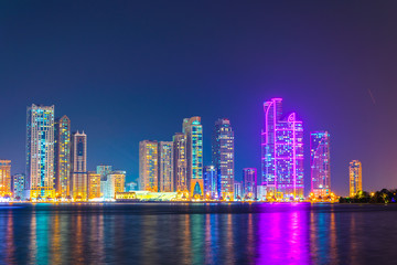 Skyscrapers surrounding the Al Majaz amphitheater situated on an artificial island in Sharjah during night, UAE