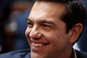 Greek PM Tsipras smiles during a session of the ruling Syriza party parliamentary group at the parliament in Athens