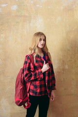 schoolgirl or young girl in red checkered shirt with backpack