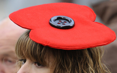 An onlooker wearing a poppy design hat watches the annual Remembrance Sunday ceremony in central London