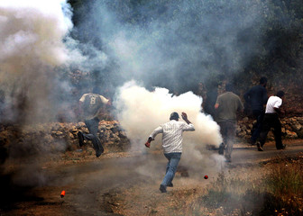 Palestinians run after Israeli forces fire stun grenade and teargas canisters during protest against ...