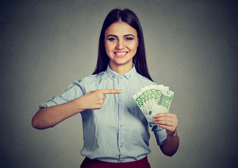 Money. Business woman looking at camera pointing at cash