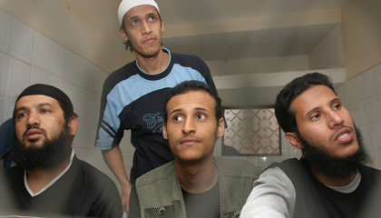Defendants look out from behind screen bars of an appeals state security court in Sanaa