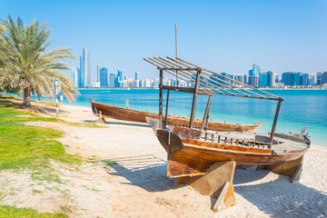 Photo sur Aluminium Abou Dabi Wooden boat at the Heritage Village, in front of the Abu Dhabi skyline, United Arab Emirates