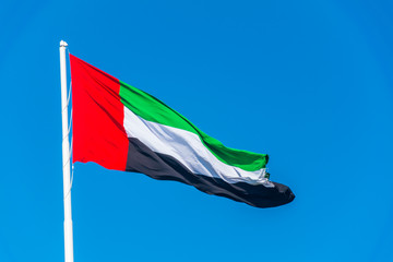 Emirates flag waving against clean blue sky