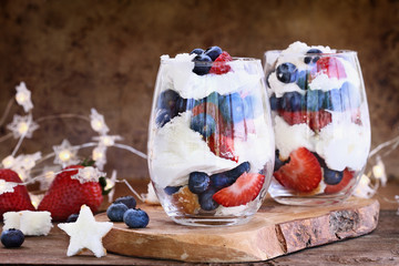 Trifle made with blueberries, strawberries, whipped cream and star shaped pound cake against a rustic background. Perfect for fourth of July. Shallow depth of field with selective focus.
