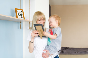 Young mother looks at photo frame with baby kid.