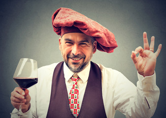 happy elegant man holding a glass of red wine