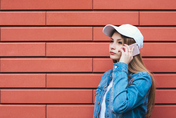 Outdoor portrait hipsterascho girl talking on the phone on a bright background. Stylish blonde woman in a denim jacket and cap talking on the phone in the background. Looking towards
