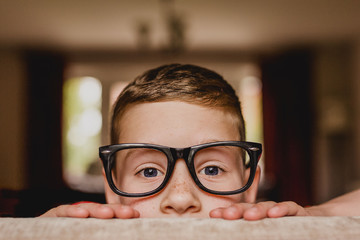 Portrait of peeking boy wearing oversized glasses Fotoväggar