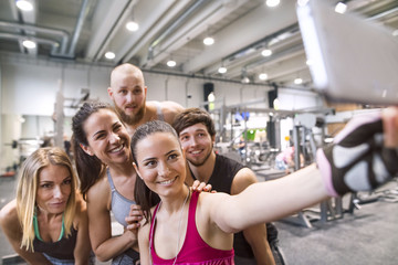 Group of young athetes taking selfies in gym