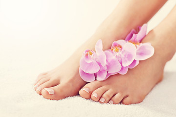 Soft female feet with french pedicure and flowers close up