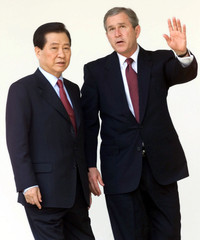 U.S. President George W. Bush talks with South Korean President Kim Dae-jung while they walk from th..