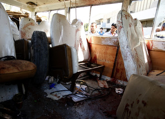 Residents look at a damaged bus after a triple bomb attack in Baghdad