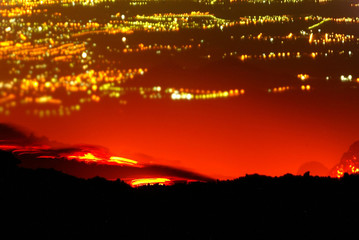 The city lights of Catania are seen in the background as lava and smoke rises from Mount Etna on the..