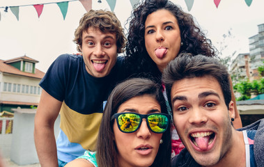 Close up of young happy people looking at camera and sticking out tongues fun in a summer party outdoors. Young people lifestyle concept.