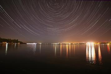tracks of stars in night sky above river
