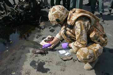 British soldier investigates at a suicide blast site in Kabul