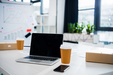 laptop computer, smartphone and coffee cups on workplace in empty office, small business office