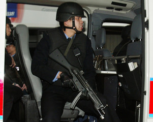 ARMED POLICEMEN SIT INSIDE A POLICE WAN WHILE ESCORTING PAKISTANIS INHONG KONG.