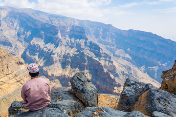 """A man is sitting on the edge of """"the grand canyon of middle east"""" at the Jebel Shams mountain in Oman"""