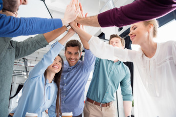 business team giving highfive together on workplace in office, young professional group concept