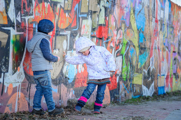 Blue eyed sibling - boy and girl - walking next to wall of graffiti in Kyiv