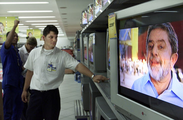 BRAZILIAN ELECTRONICS STORE WORKERS WATCH PRESIDENTIAL CANDIDATE JOSESERRA ON TELEVISION.