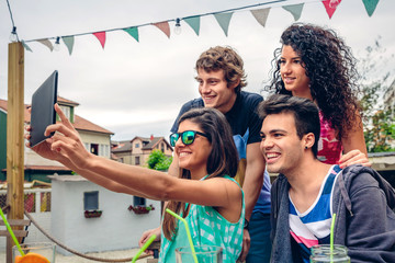 Young happy people taking a selfie with a electronic tablet in a summer party outdoors. Young people lifestyle concept.
