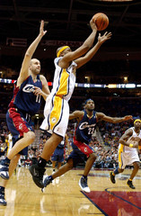 Indiana Pacers Tinsley gets off a shot as Cleveland Cavaliers Ilgauskas attempts to block in their NBA game in Cleveland
