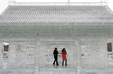 Tourists walk inside ice-sculpted replica of a Chinese traditional construction during China Harbin international ice and snow festival