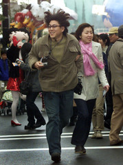 JAPANESE COUPLE DASH INTO UNIVERSAL STUDIOS JAPAN AT ITS GRAND OPENING IN OSAKA.