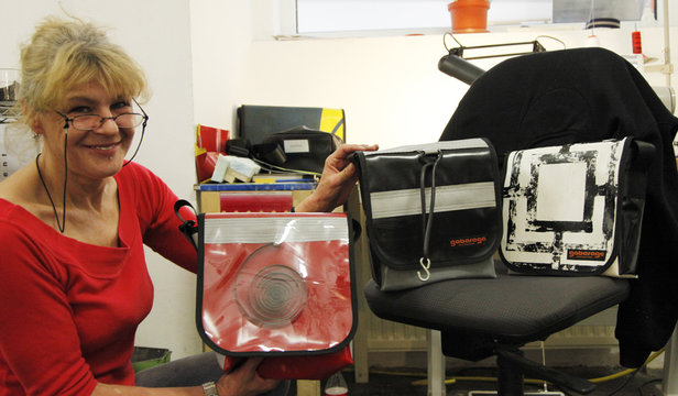 A worker presents bags made of old plastic lorry covers at the Gabarage design shop in Vienna