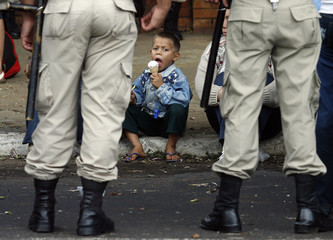 A Paraguayan homeless boy eats an ice cream as he and several hundred members of the  Homeless Movement were stopped by riot police in Asuncion