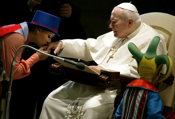 An artist from the Canadian circus 'Cirque du Soleil' kisses Pope John Paul II's hand during his wee..