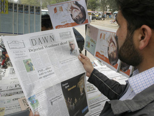 A man reads a newspaper with the news of Pakistan's cricket coach Bob Woolmer's death at a roadside stall in Islamabad