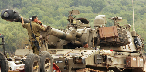 Israeli soldiers load a tank onto a trailer as they continue their withdrawal from the Israeli-Lebanon border