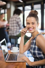 Portrait of beautiful woman using laptop in restaurant