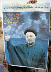 Iraqi soldier displays a poster of the leader of an Iraqi cult in Najaf