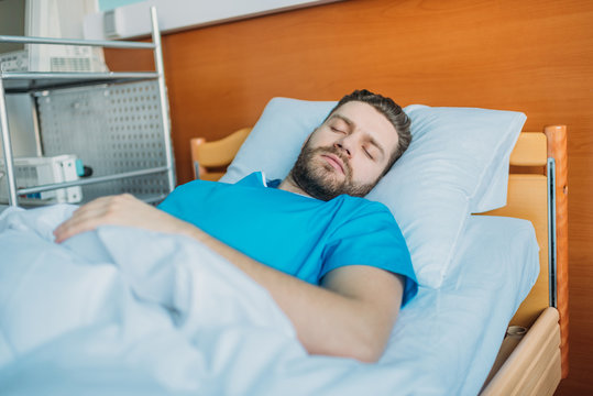 young sick man sleeping on hospital bed at ward, hospital patient bed