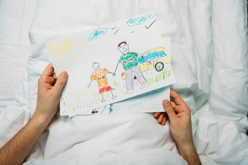 sick father holding drawings while laying on hospital bed at ward, hospital patient bed
