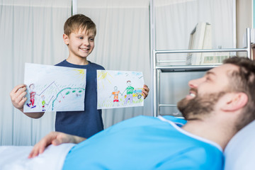 little son showing sick father his drawings at ward, dad and son
