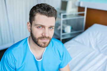 Portrait of sick bearded man sitting on hospital bed and looking at camera