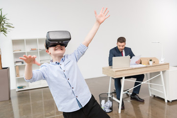 Boy using virtual reality glasses while his father businessman working in office