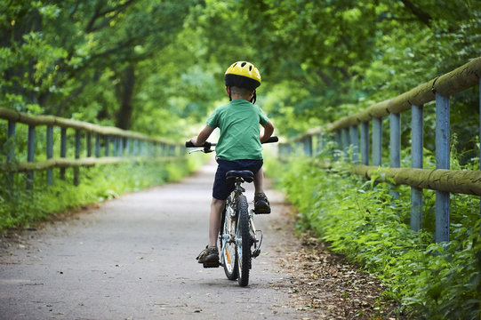 Child boy on a bicycle on bicycle path in summer. Boy cycling outdoors in safety helmet