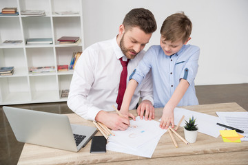 Businessman with son drawing at table in office
