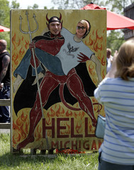 Visitors pose for a picture behind a sign in Hell