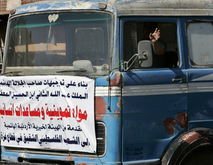 A Jordanian driver waves from one of the trucks loaded with humanitarian aid before they depart for the Gaza Strip, as part of an aid corridor ordered by Jordan's King Abdullah II to help impoverished Palestinians in the territories, in Amman